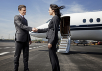 Businessman and businesswoman shaking hands on runway nearby plane