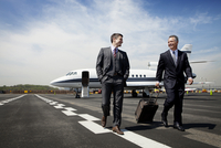 Two businessmen walking away from jet plane along runway