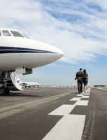 Couple walking on tarmac by jet