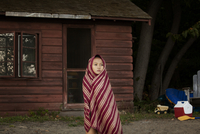Girl (8-9) wrapped in blanket standing in front of log cabin