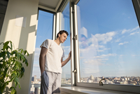Man in pajamas looking through window at cityscape