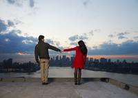 Young couple holding hands on rooftop at dusk