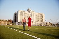 Two men walking in sport field