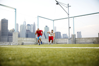 Two men running in sport field cityscape in background