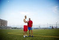 Portrait of two men standing in sport field