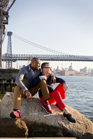 Two happy men sitting on promenade with Brooklyn Bridge in background