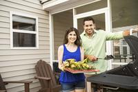 Couple barbequing corn and burgers in backyard 11100002430| 写真素材・ストックフォト・画像・イラスト素材|アマナイメージズ