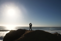 Young couple standing on rock with sea in background
