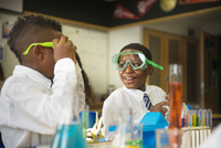 School boys (8-9) in science class, wearing safety goggles