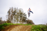 Motocross rider performing trick on dirt road