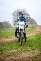 Female motocross rider posing in front of dirt road