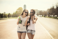 Two young women walking in city and laughing