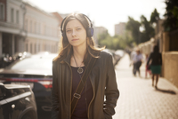 Woman with headphones walking along street