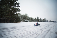 Go-cart driver on snowy road