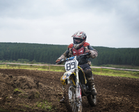 Boy (10-11) motocross riding on dirt road