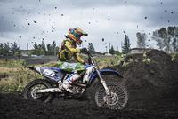 Man motocross riding on dirt road