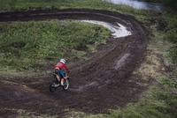 Boy (12-13) motocross riding on dirt road