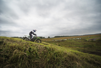 Man motocross riding on green hill