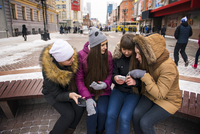 Young women sitting on street bench looking at smart phone,