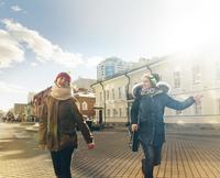 Girl (12-13) and teenage girl (14-15) on city sunlit street