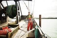 Young man holding crab cage on fishing boat