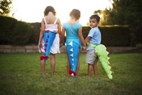 Children (2-3, 4-5, 6-7) wearing dinosaur tail costumes in backyard