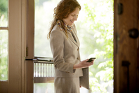 Businesswoman leaving home checking phone 11100005171| 写真素材・ストックフォト・画像・イラスト素材|アマナイメージズ