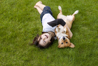 Girl (8-9) and pet corgi rolling on lawn