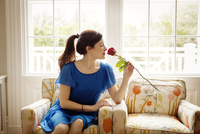 Woman smelling rose at home