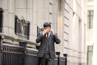 Stressed businessman using cell phone on street