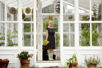 Portrait of woman holding sunflower in her greenhouse