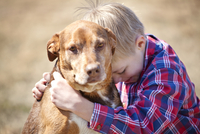 Young blond boy(8-9) hugging his dog