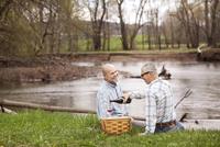 Gay couple having picnic at lake 11100007411| 写真素材・ストックフォト・画像・イラスト素材|アマナイメージズ