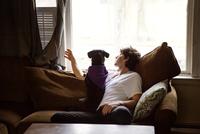 Young man sitting on sofa with dog and looking through window 11100008415| 写真素材・ストックフォト・画像・イラスト素材|アマナイメージズ