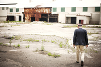 Rear view of man wearing hardhat walking towards old warehouse