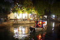 Boat floating down canal at night