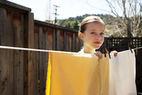 Portrait of girl (8-9) hanging up clothes on laundry line