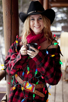 Woman covered in Christmas lights with coffee