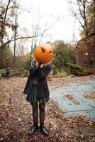 Young woman posing with jack-o-lantern on her face 11100010964| 写真素材・ストックフォト・画像・イラスト素材|アマナイメージズ