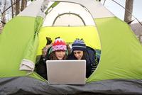 Female friends using laptop in tent 11100011125| 写真素材・ストックフォト・画像・イラスト素材|アマナイメージズ