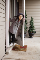 Girl (6-7) leaning out front door