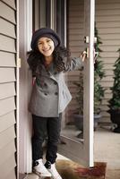 Smiling girl holding house door ajar 11100011389  写真素材・ストックフォト・画像・イラスト素材 アマナイメージズ