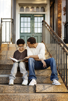 Father helping son (10-11) with schoolwork