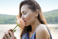 Young woman smelling rose