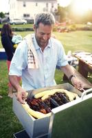 Man preparing barbecue girl