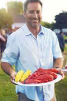 Man holding plate of lobsters and corn 11100011648| 写真素材・ストックフォト・画像・イラスト素材|アマナイメージズ