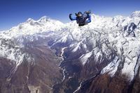 Skydiver jumping over snow-covered mountains