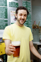 Brewery worker holding pint of beer
