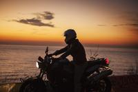 Man on motorbike by sea at sunrise