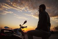 Man on motorbike at sunrise